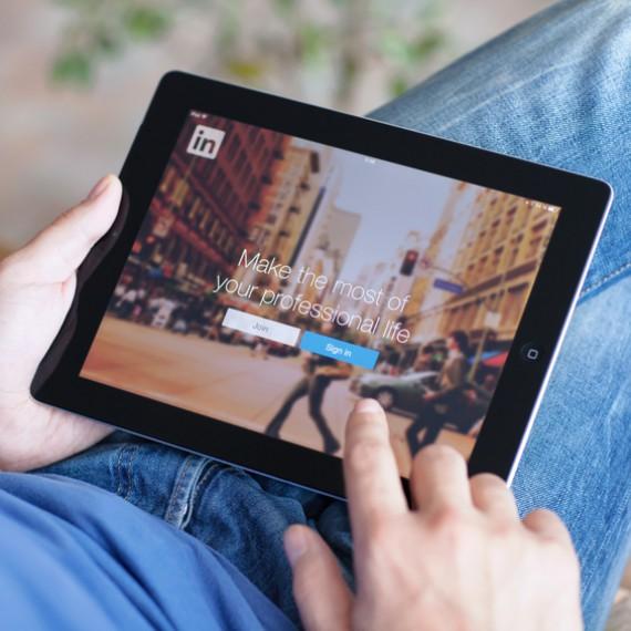 Man holding iPad with App LinkedIn on the screen