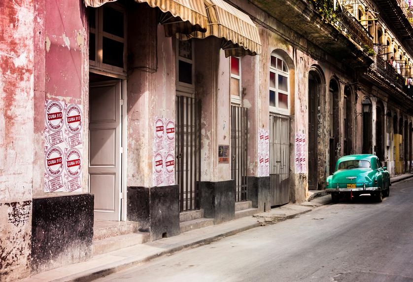 Green vintage car parked along Havana, Cuba street