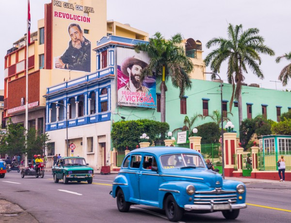 Street with oldtimers and propaganda in Santiago de Cuba